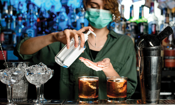 A bartender pours hand sanitizer into her hands as she prepares to serve drinks.